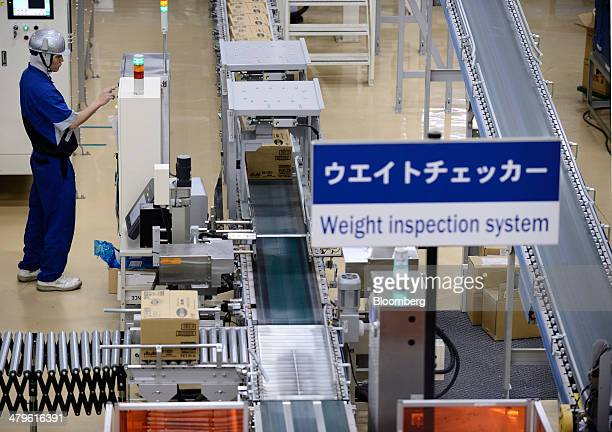 An Asahi Soft Drinks Co employee operates machinery as boxes containing bottled beverage moves along the production line of the company's Mount Fuji...