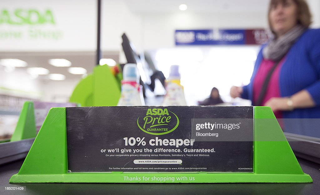 An Asda shopping divider sits on the conveyor belt of a check-out desk inside an Asda supermarket, the U.K. retail arm of Wal-Mart Stores Inc., in Watford, U.K., on Thursday, Oct. 17, 2013. U.K. retail sales rose more than economists forecast in September as an increase in furniture demand led a rebound from a slump the previous month. Photographer: Simon Dawson/Bloomberg via Getty Images