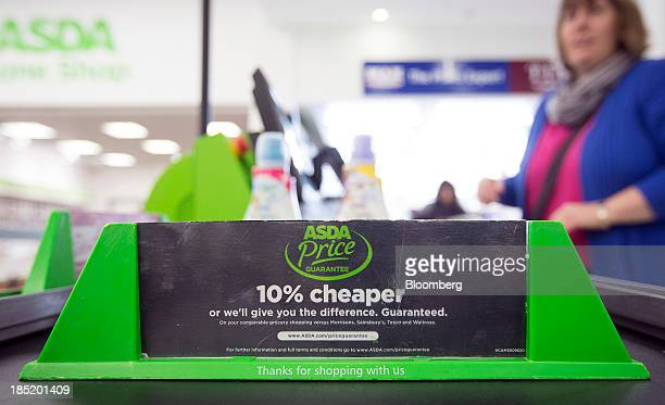 An Asda shopping divider sits on the conveyor belt of a checkout desk inside an Asda supermarket the UK retail arm of WalMart Stores Inc in Watford...