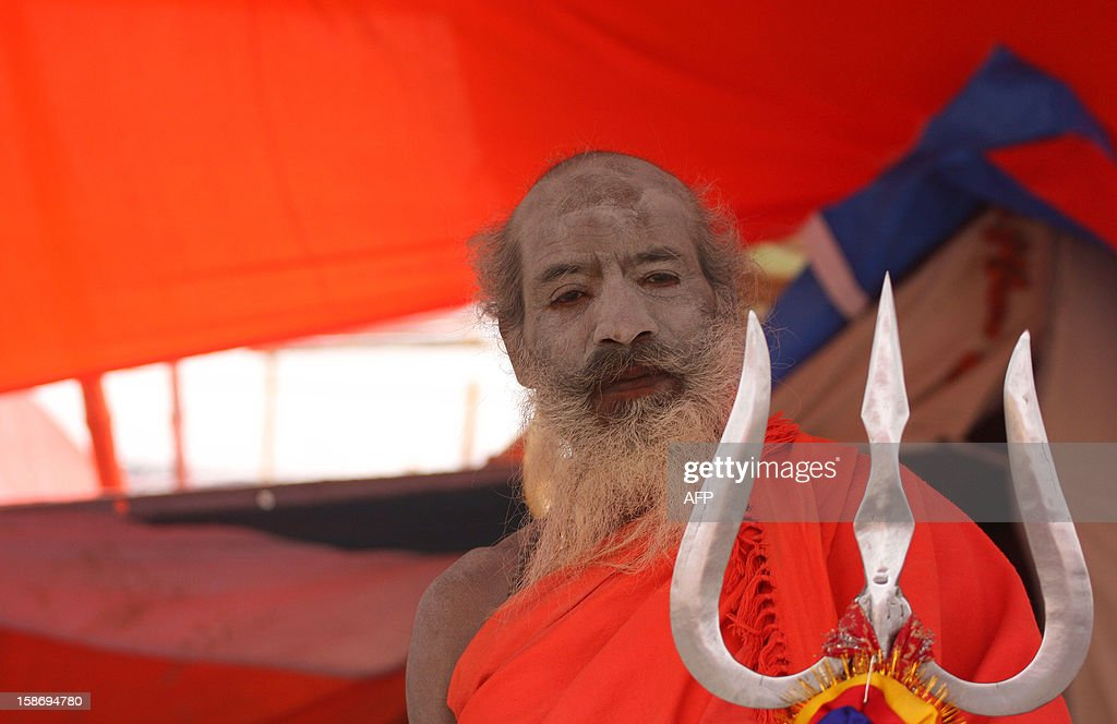 An ash smeared Hindu Sadhu or holy man poses inside a tent at the confluence of the Rivers Ganges, Yamuna and mythical Saraswati in Allahabad on December 24, 2012, ahead of The Maha Kumbh Mela. The Kumbh Mela, which is scheduled to take place in the northern Indian city in January and February 2013, is the world's largest gathering of people for a religious purpose and millions of people gather for this auspicious occasion. AFP PHOTO/ Sanjay KANOJIA