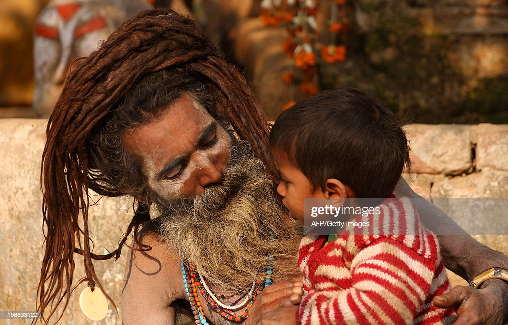 An ash smeared Hindu Sadhu or holy man speaks with a young boy beside a tent at the confluence of the Rivers Ganges, Yamuna and mythical Saraswati in Allahabad on December 31, 2012, ahead of The Maha Kumbh Mela. The Kumbh Mela, which is scheduled to take place in the northern Indian city in January and February 2013, is the world's largest gathering of people for a religious purpose and millions of people gather for this auspicious occasion. AFP PHOTO/ Sanjay KANOJIA