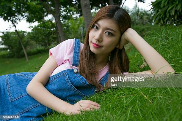 An Asian Beauty Young Woman Laying on a Grass Field