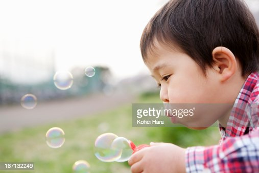 an asian boy blowing soap-bubbles : Stock Photo