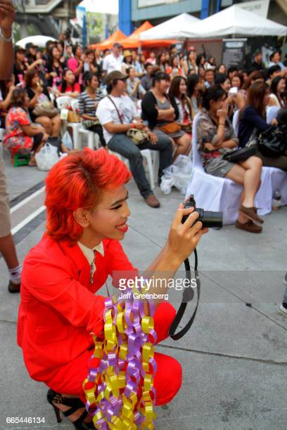 An Asian cross dresser with red dyed hair taking pictures of a talent show at the MBK Center