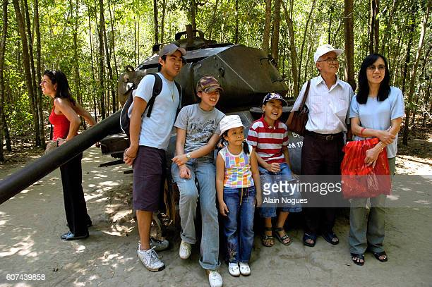 An Asian family pose for a photograph in front of a tank destroyed by the Vietcong in Cu Chi