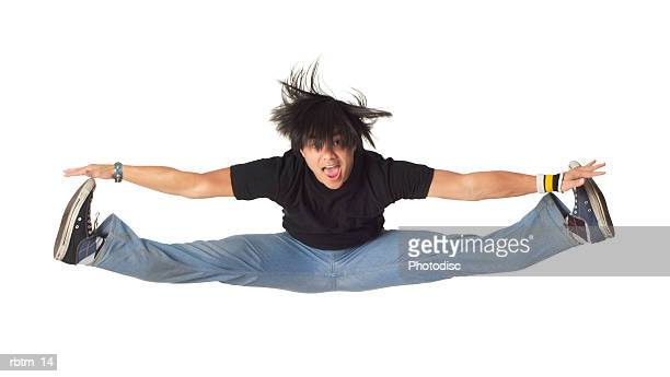 an asian male teen in jeans and a black shirt jumps up and does the splits in the air