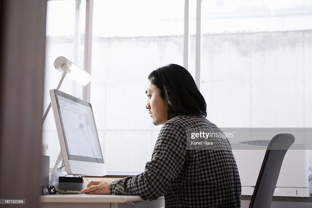 an asian man working at office
