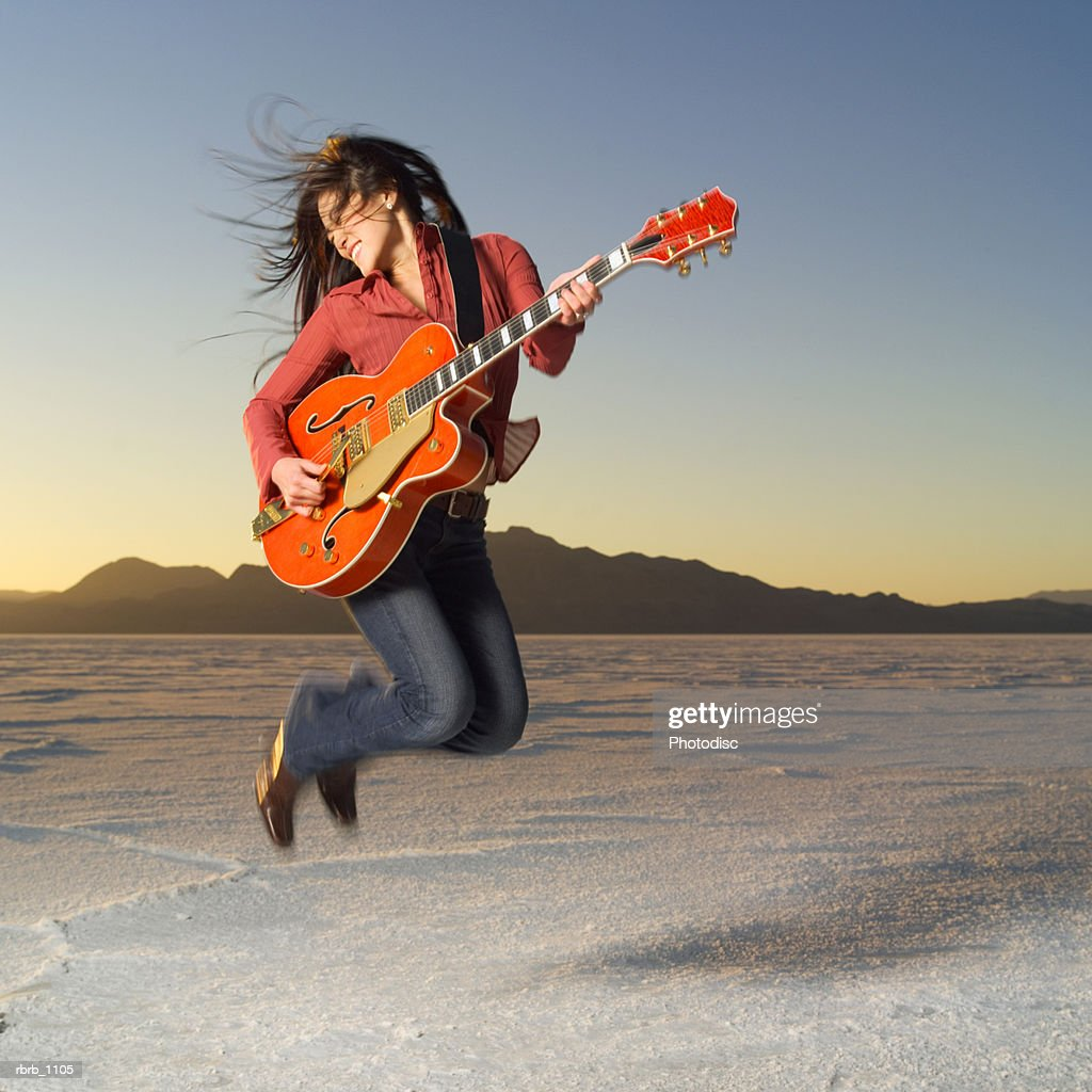 an asian teenage girl in jeans and a red shirt jumps up with a guitar in a desert : Stock Photo