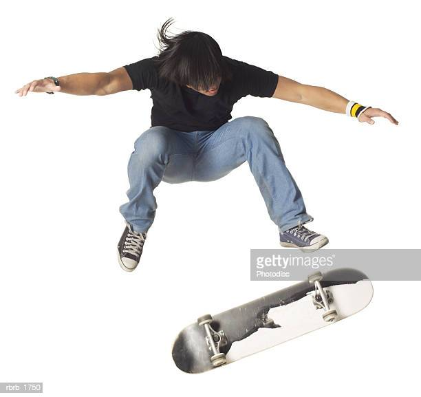 an asian teenage male in jeans and a black shirt jumps up wildly on his skateboard