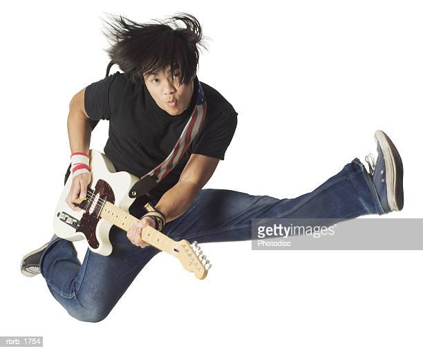 an asian teenage male in jeans and a black shirt jumps up wildly with his electirc guitar