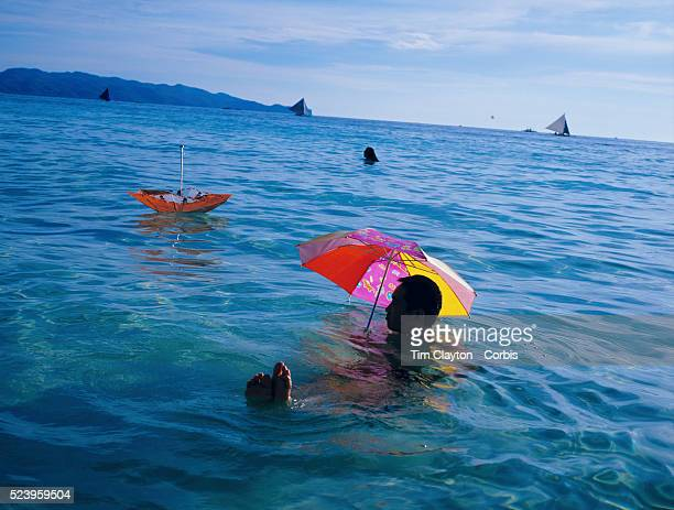 An asian tourist enjoys the pristine waters of White Beach while protecting himself from the sun with umbrella in Boracay Island the Philippines The...