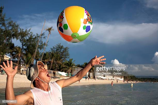 An asian tourist plays with an inflatable ball in the pristine waters of White Beach in Boracay Island the Philippines The 4 km stretch of White...