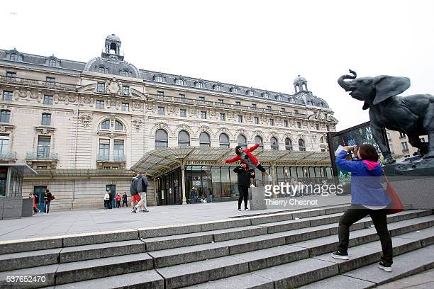 An Asian tourist poses in front of the Orsay museum on June 2 2016 in Paris France The Orsay museum has been closed due to the threat of flooding...