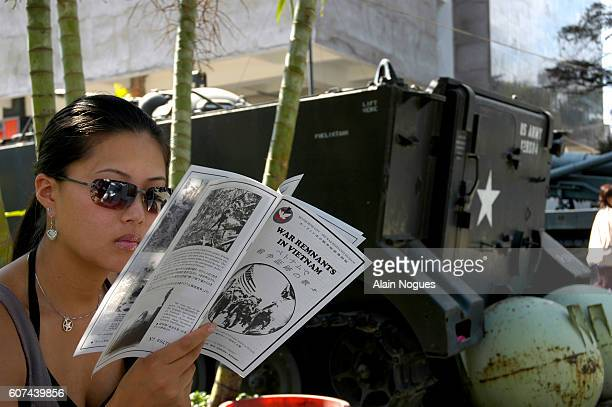 An Asian visitor reads a catalogue during a visit to the War Remnants Museum in Saigon