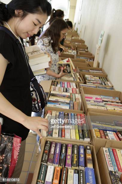 An Asian woman browsing books at the MiamiDade Public Library Book Sale