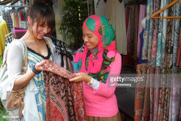 An Asian woman looking at silk scarfs in a store at Kampong Glam