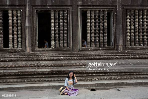 An Asian woman sits and rests besides beautiful stone carvings decorating a walkway within a gallery in Angkor Wat temple complex Siem Reap Cambodia...