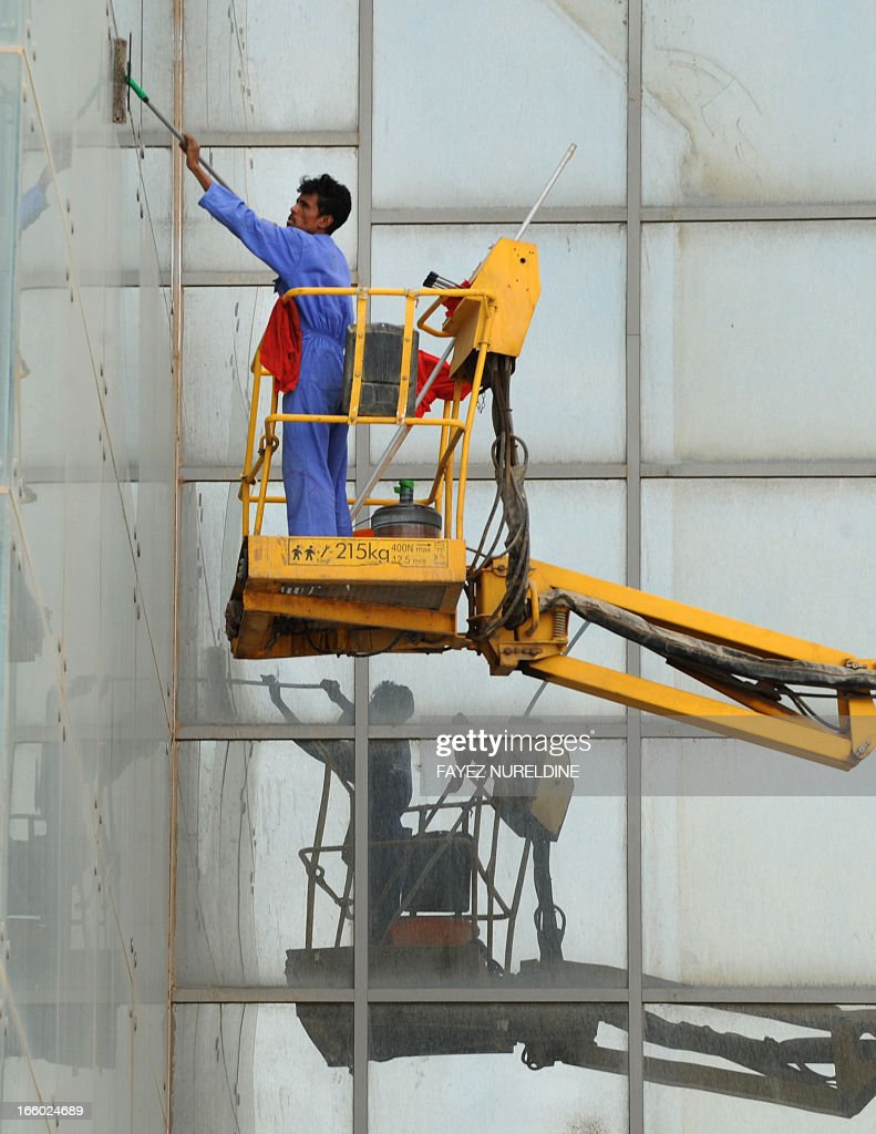 An Asian worker cleans the glass front of a highrise in the center of Saudi capital Riyadh on April 7, 2013. Saudi Arabia has given illegal foreign workers a three-month grace period to legalise their status, after panic over reported mass deportations, an official statement said. AFP PHOTO/FAYEZ NURELDINE