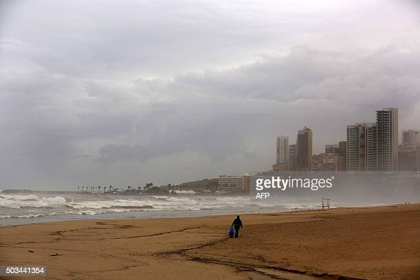 TOPSHOT An Asian worker collects rubbish from Beirut's public beach Ramlet alBaida on January 5 2016 BAZ