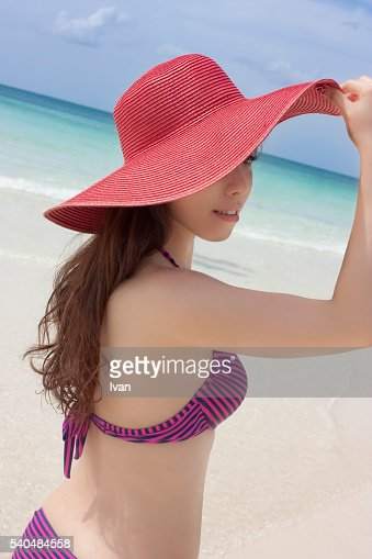 An Asian Young Woman, Girl Holding a Panama, Sun Hat and Looking Left, Covering Half of the Face Against Blue Sky and Ocean with Red Bikini