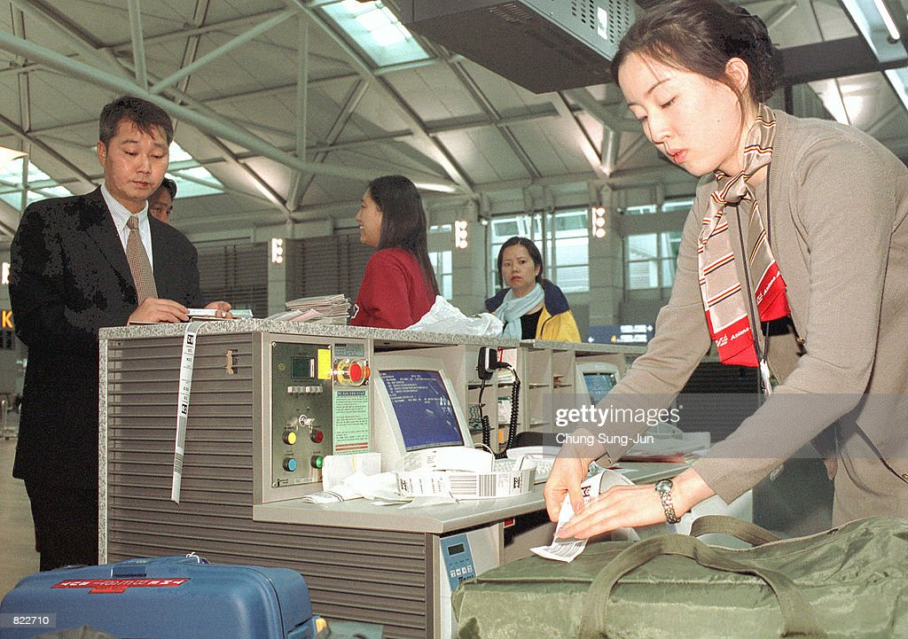 An Asiana Airline employee attaches a tag to a passenger's luggage April 5 2001 in the newly opened Incheon International Airport that lays 32 miles...