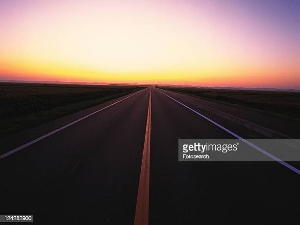 an Asphalt Road By Sunset, the Horizon Reflecting the Colors of the Sun, Front View, Hokkaido Prefecture, Japan