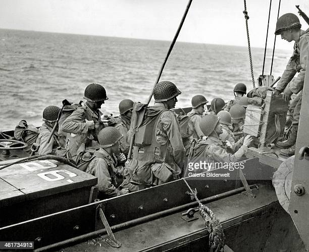 An assault unit completes boarding a Landing Craft Vehicle Personnel or the APA 26 USS Samuel Chase 6th June 1944 GIs are wearing assault vests...