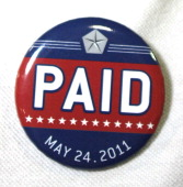 An assembly line worker wears a pin labled 'PAID' on his shirt before Chrysler Group and Fiat SpA CEO Sergio Marchionne announces the repayment of...