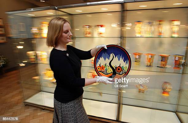 An assistant at Bonhams auction house moves a plate by acclaimed designer Clarice Cliff ahead of an auction of 100 Clarice Cliff ceramics on March 16...