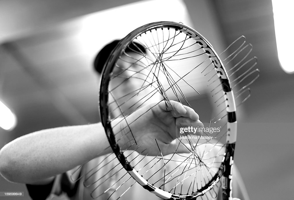 An assistant cuts out the broken strings of a damaged racquet before it is restrung at the stringers' hut at the 2013 Australian Open at Melbourne Park on January 17, 2013 in Melbourne, Australia.