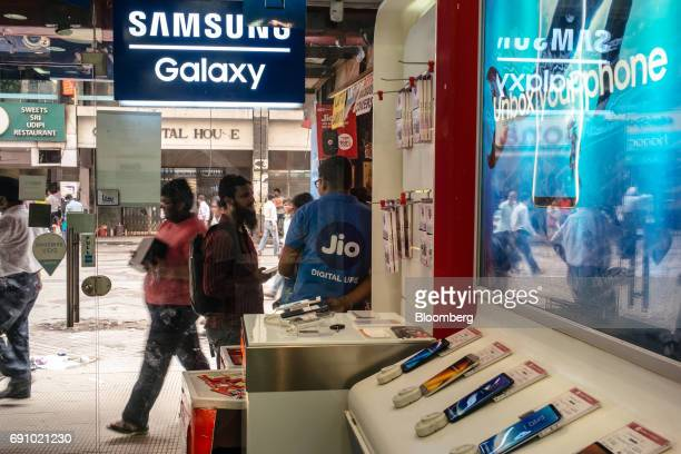 An assistant for Reliance Jio Infocomm Ltd speaks to a customer at a stall outside a store selling Samsung Electronics Co smartphones at the Nehru...