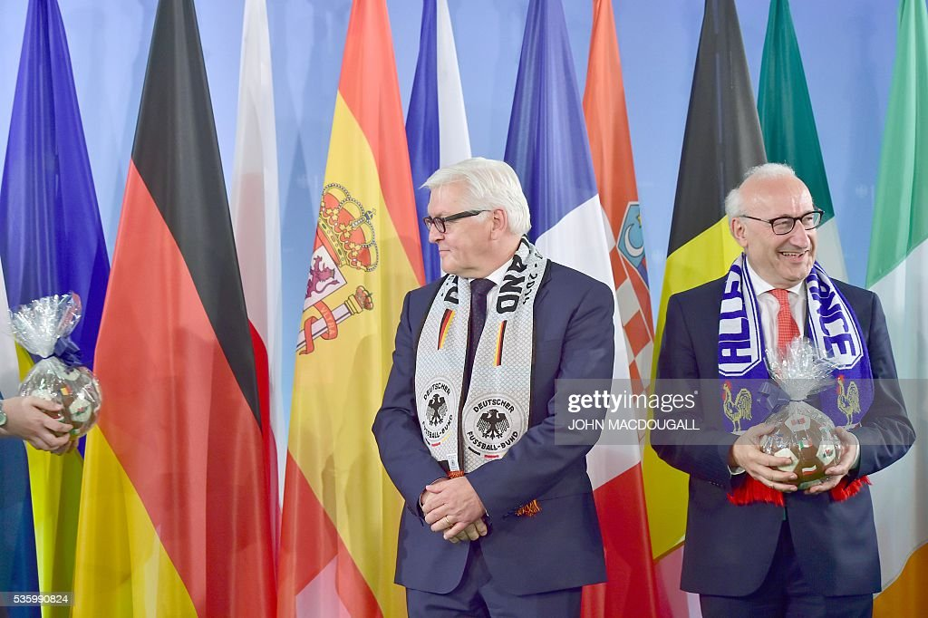 An assistant (L) hands a football made of chocolate to German Foreign Minister Frank-Walter Steinmeier (C) as French Ambassador to Germany Philippe Etienne (R) holds one during a function at the foreign ministry in Berlin on May 31, 2016, ahead of the UEFA Euro 2016 taking place in France next month. / AFP / John MACDOUGALL