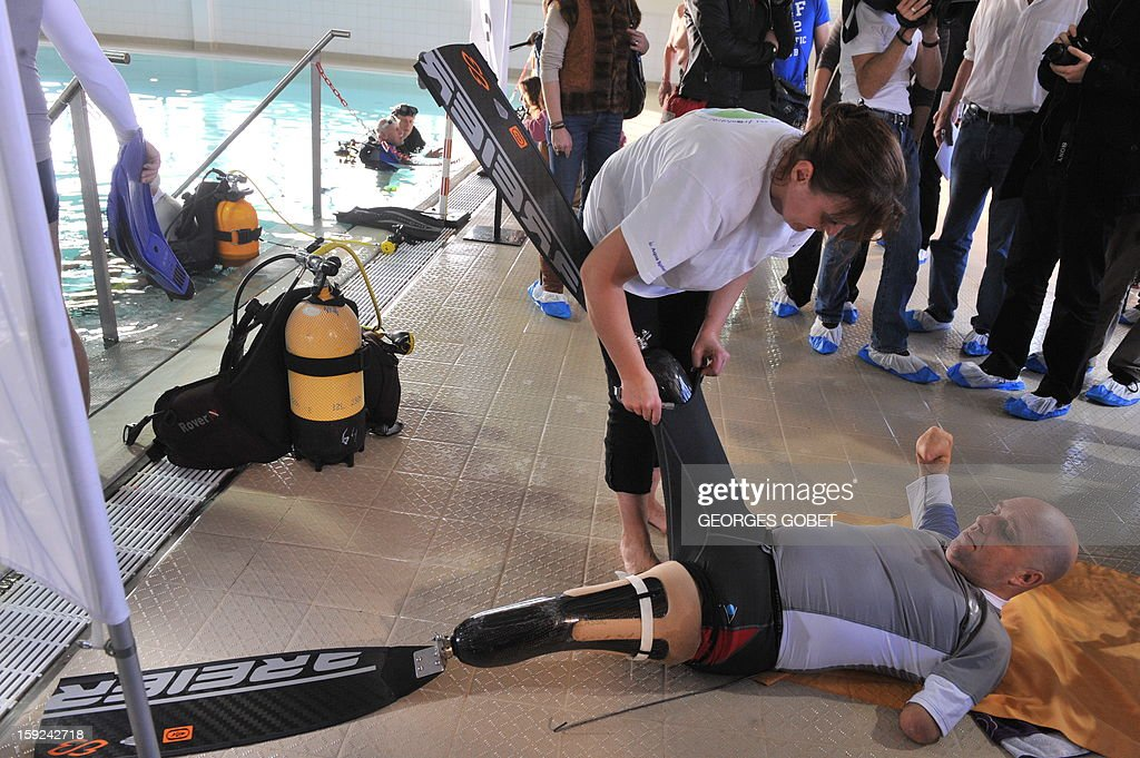 An assistant helps French Philippe Croizon (R), 44, remove on January 10, 2013 his flippers after he became the first quadruple amputee to dive at a depth of 33 meters in the deepest swiming pool in the world in Brussels. He used flippers attached to prosthetic limbs to dive to the bottom of the pool with a group of 15 Belgian divers to set a new world record for an amputee. Croizon had all four limbs amputated in 1994 after being struck by an electric shock of more than 20,000 volts as he tried to remove a TV antenna from a roof. He has swum across the English Channel and all five intercontinental channels. AFP PHOTO GEORGES GOBET