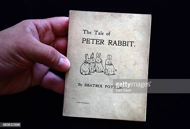 An assistant holds a first edition of The Tale of Peter Rabbit by Beatrix Potter at Dreweatts and Bloomsbury Auctions on July 27 2016 in London...