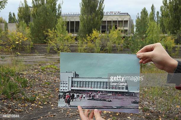 An assistant holds up a photo showing the city of Pripyat's main square and the 'Energetik' cultural center before 1986 at the same site that today...