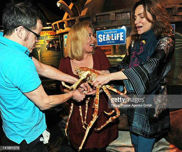 An assistant of Aqua Dome Sealife tries to free the finger of radio personality Gerlinde Jaenicke after being bitten by a japanese spidercrab during...