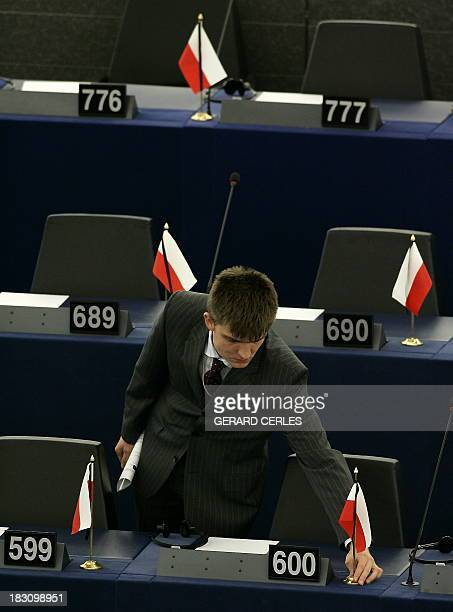 An assistant of Polish ultranationalist European Deputies installs a Polish Flag reportedly in memory of Pope John Paul II during the Plenary session...