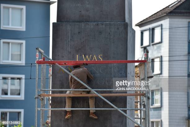 An assistant paints golden letters on Nigerianborn US artist and writer Olu Oguibe's 'Obelisk' during the Documenta 14 art exhibition in Kassel on...