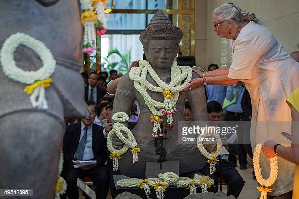 An assistant places traditional Cambodian crowns of flowers around the neck of the Balarama statue returned by Christie's auction house during an...