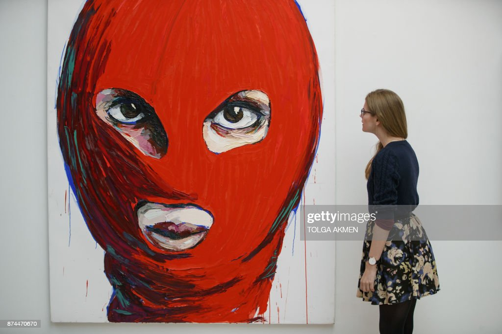 An assistant poses with 'Pussy Icons' artwork by contemporary artist Lusine Djanyan during a press preview for the 'Art Riot: Post-Soviet Actionism' and 'Inside Pussy Riot' exhibitions at Saatchi Gallery in central London on November 15, 2017. / AFP PHOTO / Tolga AKMEN / RESTRICTED