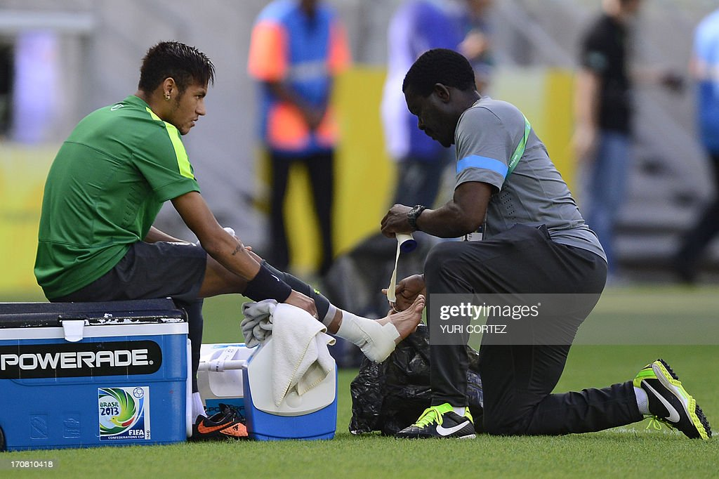 An assistant puts bandages and tape around the ankle of Brazil's forward Neymar (L) during a training session in Fortaleza, northeastern Brazil, on the eve of their FIFA Confederations Cup Brazil 2013 Group A football match against Mexico, on June 18, 2013.