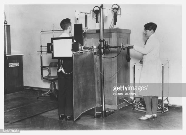 An assistant radiographer takes an xray of a patient at the Zeileis Institute using the process invented by Dr Zeileis Goldspach and Professor Lazarus