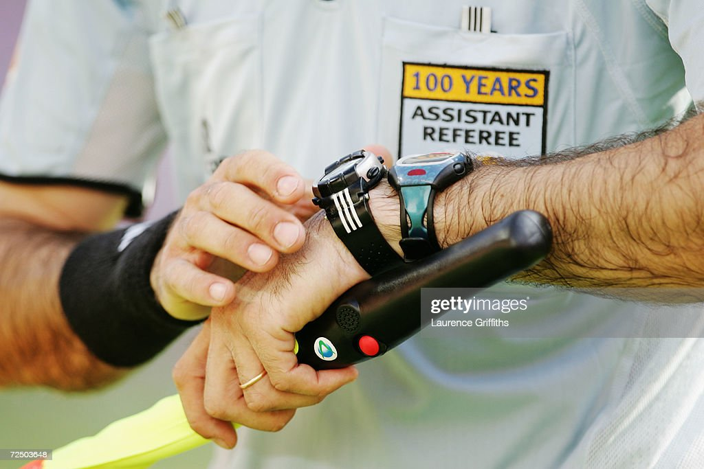 An assistant referee checks his watch during the Switzerland v Croatia Group B match in the 2004 UEFA European Football Championships at the Dr...