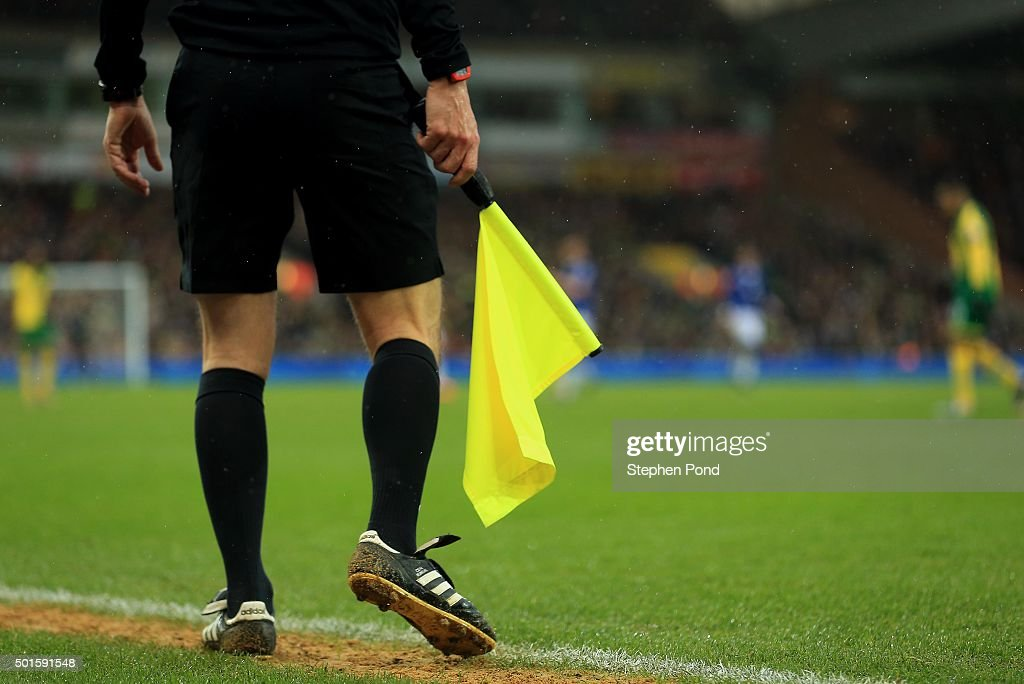 An Assistant Referee holds his flag on the touchline during the Premier League match between Norwich City and Everton at Carrow Road stadium on...