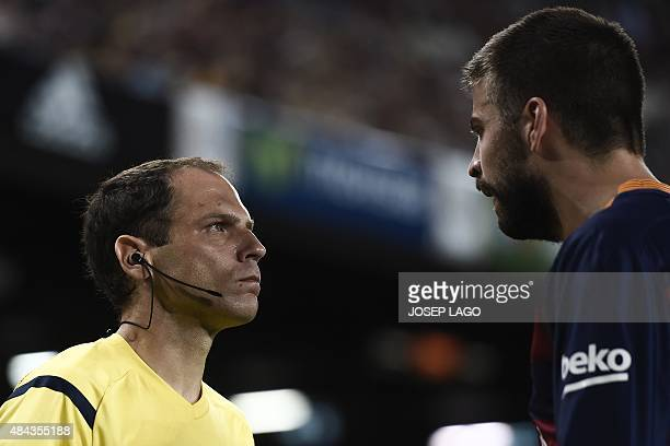 An assistant referee looks at Barcelona's defender Gerard Pique during the Spanish Supercup secondleg football match FC Barcelona vs Athletic club...