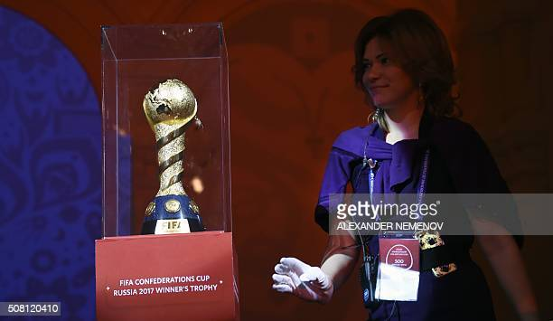 An assistant stands next to the FIFA Confederations Cup trophy during a ceremony marking 500 days until the start of the FIFA Confederations Cup 2017...