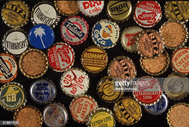 An assortment of American soda juice and beer bottle caps mostly from the 1950s and early 1960s Some are flippedover to show cork backing