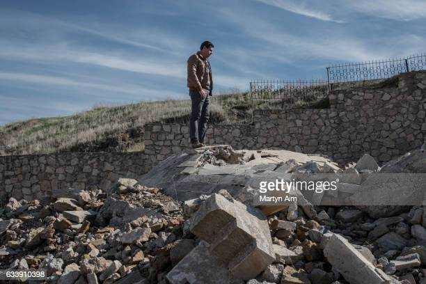 An Assyrian Catholic Iraqi man stands on top of the destroyed dome of the tomb of Mar Behnam and Mart Sarah at the Mar Behnam monastery on February 4...