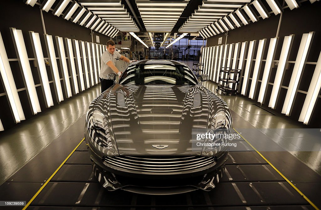 An Aston Martin Vanquish is inspected by hand inside a light booth by technician Matthew Goss at the company headquarters and production plant on January 10, 2013 in Gaydon, England. The iconic British brand is celebrating its 100th anniversary. Lionel Martin and Robert Bamford created Bamford & Martin on January 15 1913, which later became Aston Martin in honour of Bamford's wins at the Aston Clinton Hillclimb in Buckinghamshire.