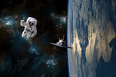 An astronaut drifting in space is rescued by a space shuttle orbiting Earth.